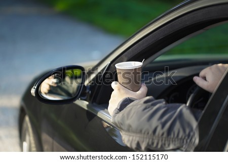 Man with coffee in car - stock photo