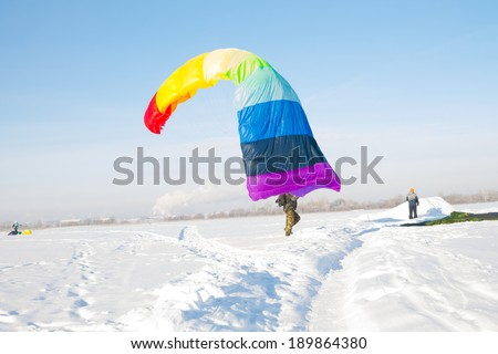 man with colorful parachute landing on white snow