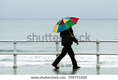 Man with colorful umbrella walking around town