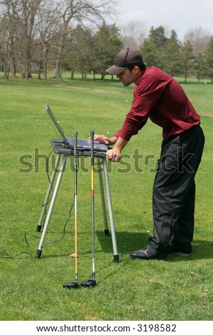 man with computer on golf-course