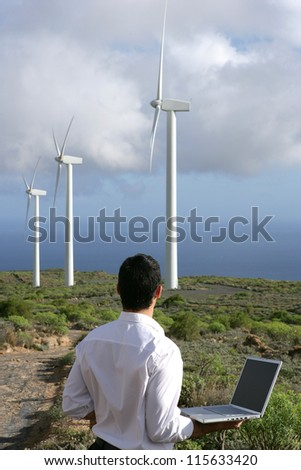 Man with computer watching wind turbines