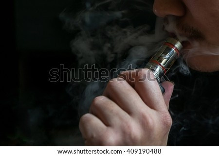 Man with concealed identity smoking a controversial vaping an electronic cigarette. Vaping is debatable in the health community if it is safe or a health risk - stock photo