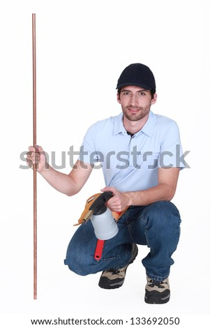 Man with copper pipe and a blowtorch - stock photo