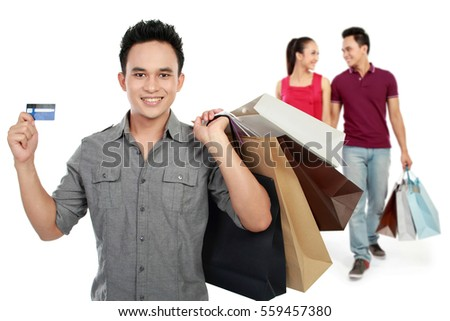 man with credit card carrying shopping bag. couple at the background
