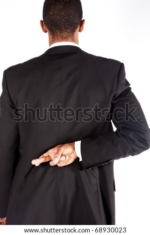 Man with crossed fingers behind his back - stock photo