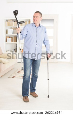 Man  with crutches, rehabilitation after injury - stock photo
