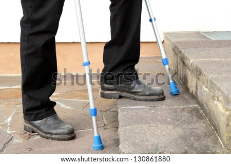 Man with crutches trying to climb some steps - stock photo