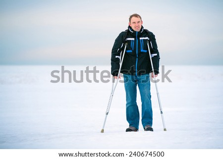 Man with crutches walking outdoors on winter day - stock photo