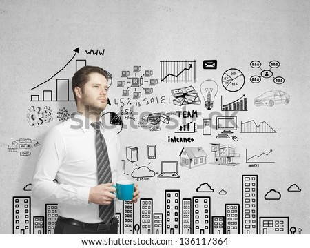 man with cup of coffee and drawing city plan - stock photo