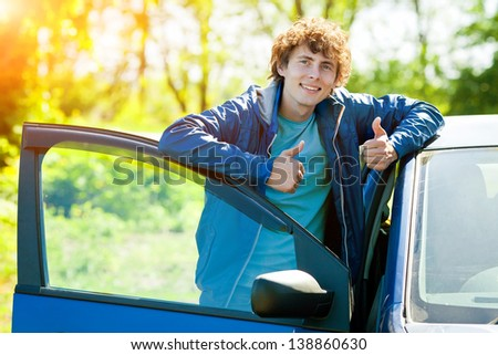 man with curly hair near automobile - stock photo
