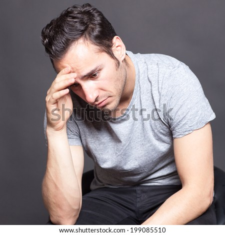 Man with depression sitting in gray shirt