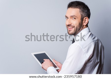 Man with digital tablet. Rear view of happy mature man in shirt and tie working on digital tablet and looking over shoulder while standing against grey background - stock photo