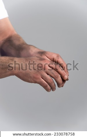 man with dirty hands on grey background. closeup picture on dirty hands with palms down