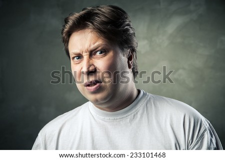 Man with disgusted expression over dark grey background - stock photo