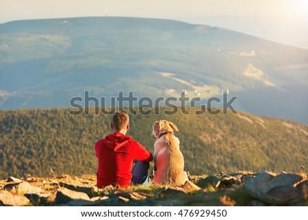 Man with dog on the trip in the mountains. Young tourist and his dog are resting and together watching the sunset.