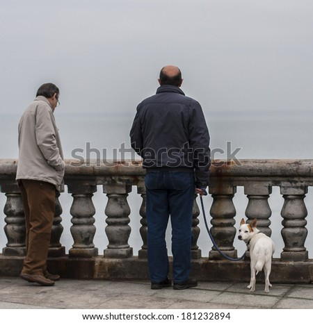 Man with dog waterfront - stock photo