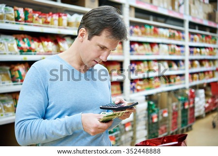 Man with dollars and calculator considers costs in the store - stock photo