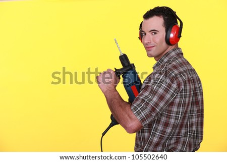 Man with drill and earmuffs - stock photo