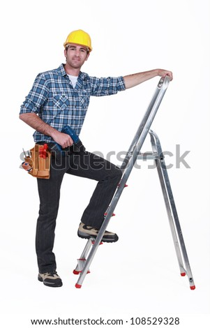Man with drill climbing ladder - stock photo