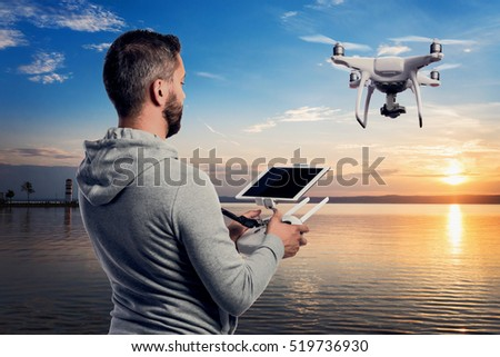 Man with drone with camera taking photos of beautiful sunset