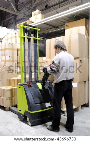 Man with electric forklift stacker truck in warehouse loading Group of cardboard boxes - stock photo
