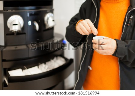 Man with espresso taking a break in front of the coffee vending machine. - stock photo