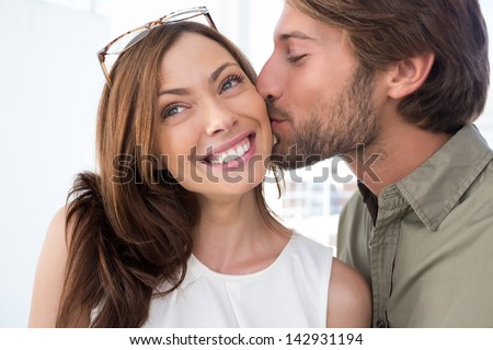 Man with facial hair kissing pretty woman on the cheek - stock photo