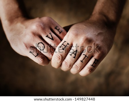 Man with (fake) Love and Hate knuckle tattoos. - stock photo