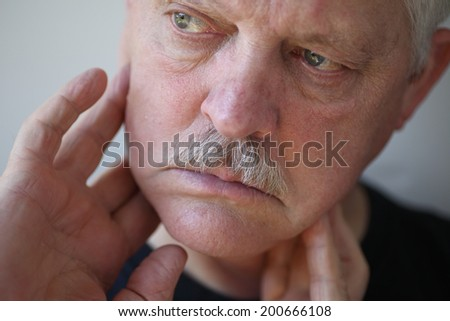 Man with fingers on painful jaw - stock photo