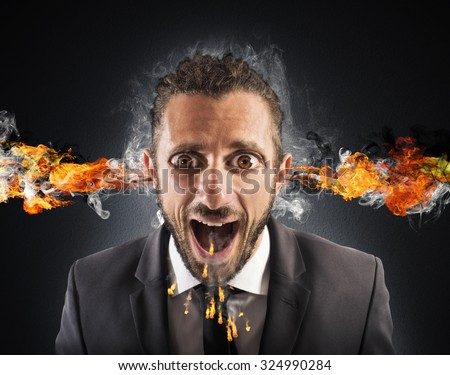 Man with fire coming out of ears - stock photo
