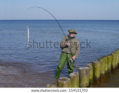 man with fish and  fishing-rod on sea background