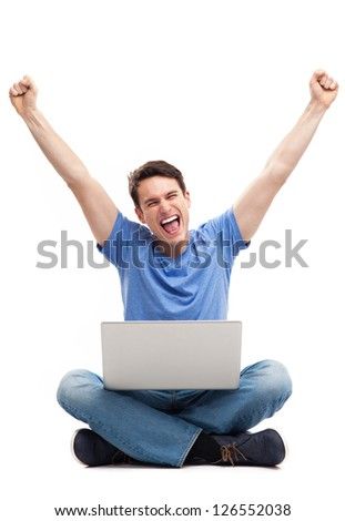 Man with fists up using laptop - stock photo