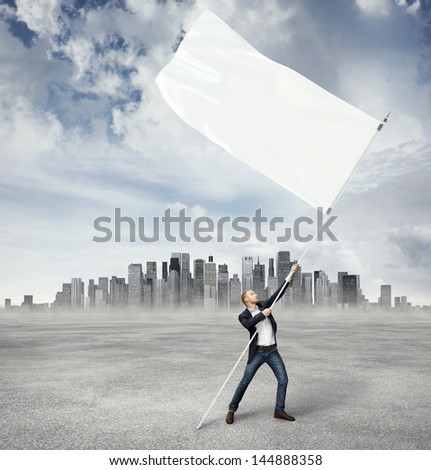 Man with flag and city on a horizon - stock photo