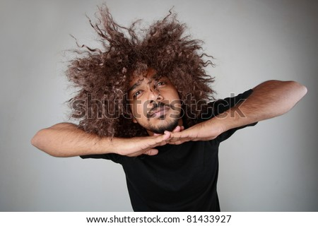 Man with funky hairstyle gives an unusual pose