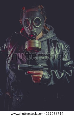 Man with gas mask and gun, dressed in black leather jacket - stock photo