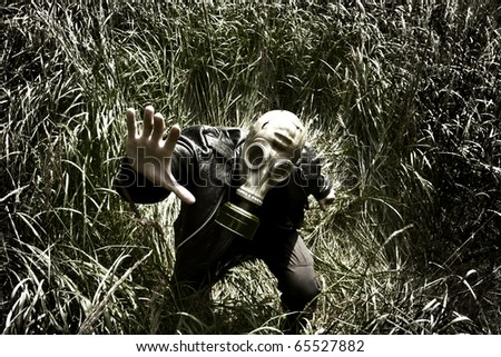 man with gas mask in the grass - stock photo
