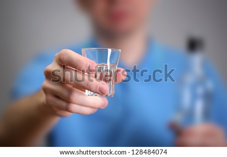 Man with glass of alcohol, on grey background