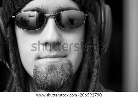 man with glasses headphones and dreadlocks - stock photo