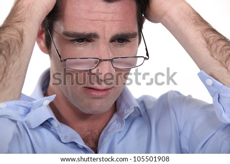man with glasses lowered on his nose looking annoyed