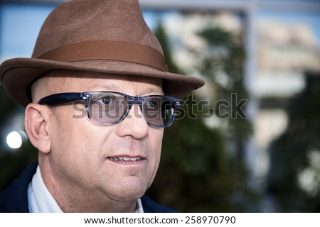 Man with glasses smiling in front of the camera, a happy man