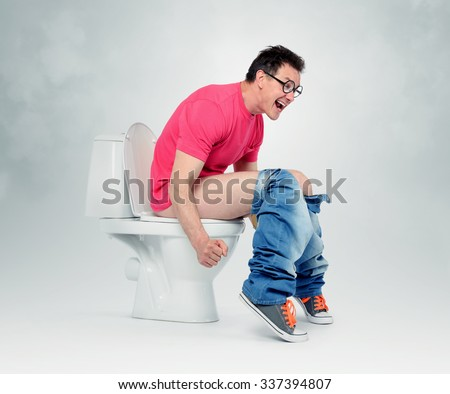 Man with glasses straining on the toilet. The concept of situation