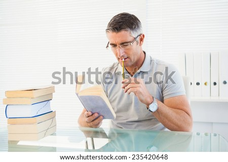 Man with glasses thinking and reading a book in his office
