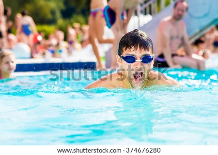 Man with goggles swimmning in the pool. Summer heat, water.