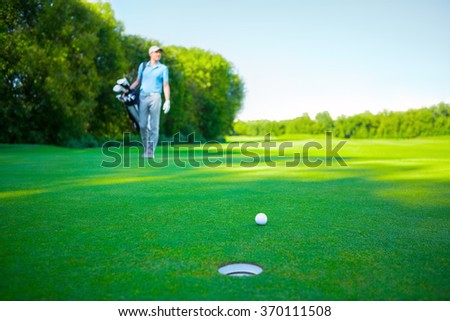 Man with golf clubs outdoors - stock photo