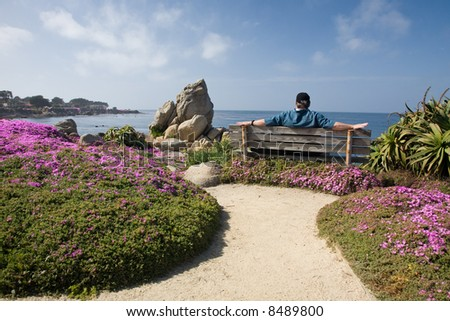 Man with graying brown hair wearing a hat, relaxing by the seaside on a bench, surrounded by rocks, flowers and greenery.  Spring or summertime setting. - stock photo