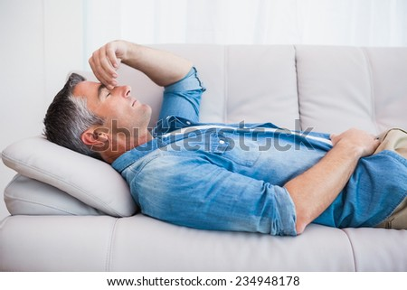 Man with grey hair relaxing on the couch at home in the living room