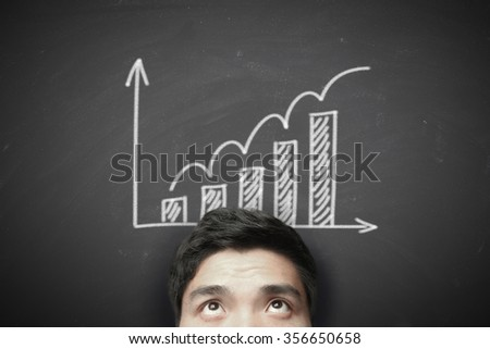 Man with growth graph on the blackboard background. - stock photo