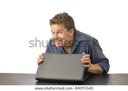 Man with guilty grin carefully closes laptop