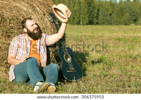 man with guitar and beer on the nature