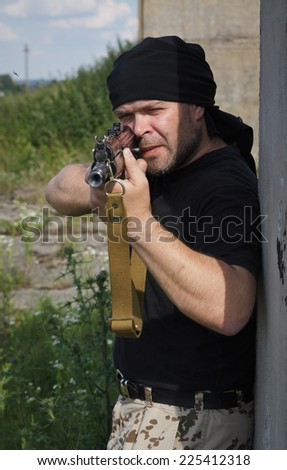 Man with gun is hiding behind the wall. - stock photo